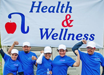 Spring Challenge Winners posing in front of the Allan Bros. Health & Wellness sign.