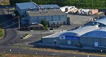 An aerial view of the northwest side of the Allan Brothers Fruit packing facilities along Highway 12.