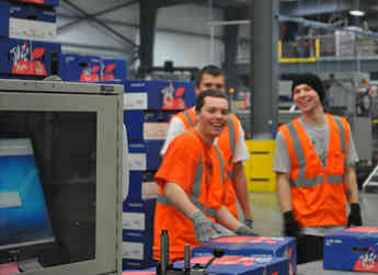 Employees work to palletize Jazz™ apples for an export fruit order.